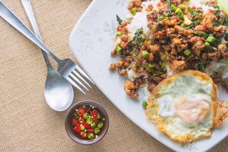 Top View of Rice topped with stir-fried pork and basil with Fried Egg on On Tablecloths sack.