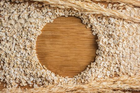 Oat Flakes on Wooden Background in Shape of Circle. Фото со стока