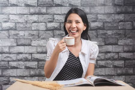 Asian women who are enjoying coffee and reading favorite books. Фото со стока