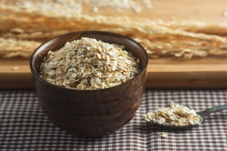 Close up of Oatmeal on the cutting board for cooking and dry rice on Table. Фото со стока