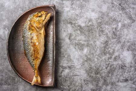 Top Table View of Fried mackerel on a semi-circular plate with space for text. Фото со стока