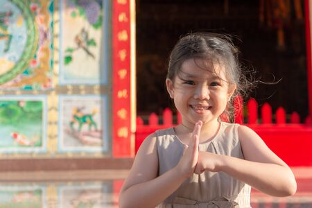 Portrait Cute Little Asian Girl Pay Respect in Shrine and Brown Dress.
