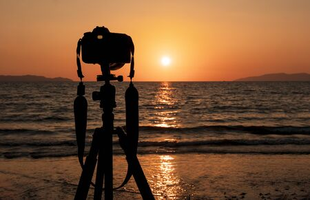 Silhouette of DSLR camera on tripod on Andaman Sea Thailand.