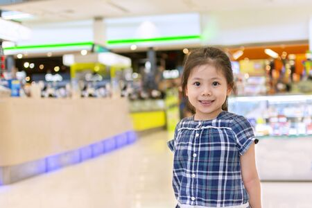 Portrait Cute girl blue grid pattern Dress smiled happily. In the mall with Space for Text. Фото со стока