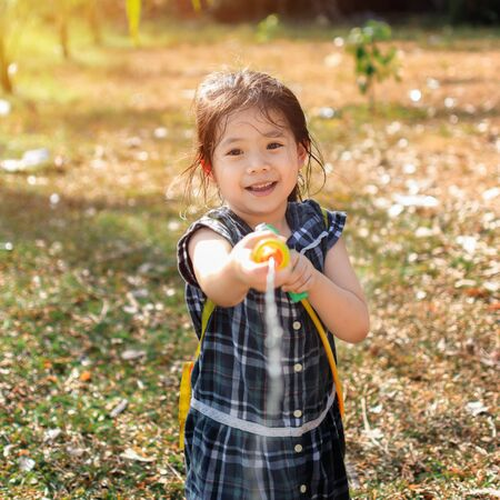 Portrait Cutle Little Asian Girl Play a fun water gun on the lawn In the summer of April. Фото со стока