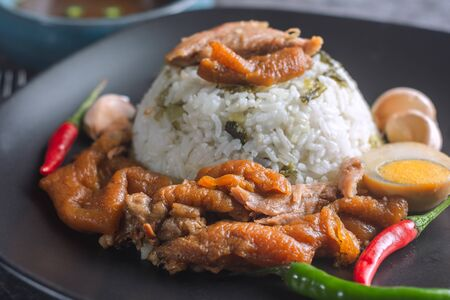 Close up of Stewed Pork Leg on Rice on Black Plate  And flavoring such as chili, garlic Ready to eat. Фото со стока