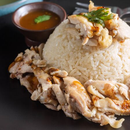 Close up of Hainanese Chicken Rice with spicy sauce on Black Plate.