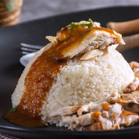 Close up of Hainanese Chicken Rice Topped with spicy sauce on Black Plate. Фото со стока