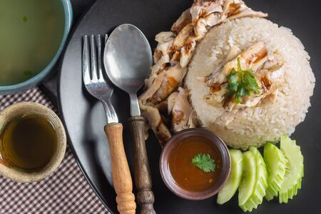 Top View of Hainanese chicken rice with Soup and sauce With hot tea on Table.