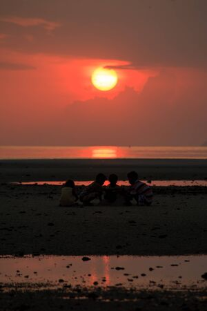 The children are playing the sand at sunset