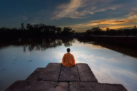angor: monk sit on the shore at angor wat ,cambodia in the twilight time. Stock Photo