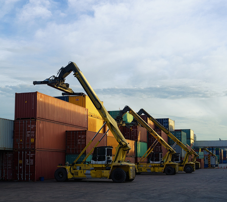 Three lift stacker in depot handling container box loading at the Docks with Truck.