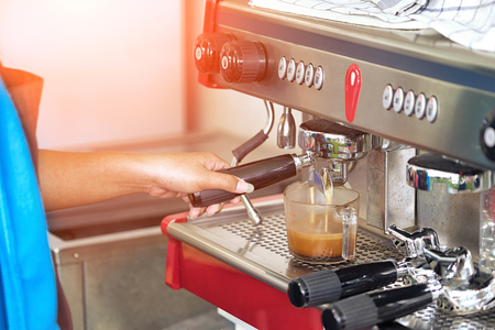Side view female making fresh espresso in coffee maker ,coffee machine preparing fresh coffee and pouring into the cup. Zdjęcie Seryjne