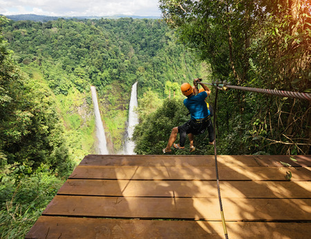 Two freedom adult Man Tourist Wearing Casual Clothing On Zip Line Or Canopy Experience In Laos Rain Forest