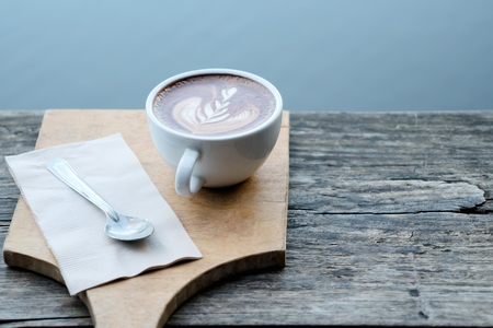 A cup of coffee with tree leaf pattern in a white cup on wooden background.