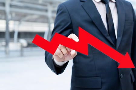 Down trend direction of graph with businessman hand holding Stock down symbol.concept of down and finance Red arrow fall dawn,economy or Stock market down,