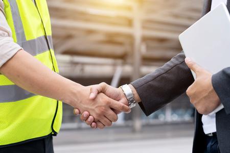 Ingenieurs schudden handen met zakenman na succesdag en vieren succes. Stockfoto