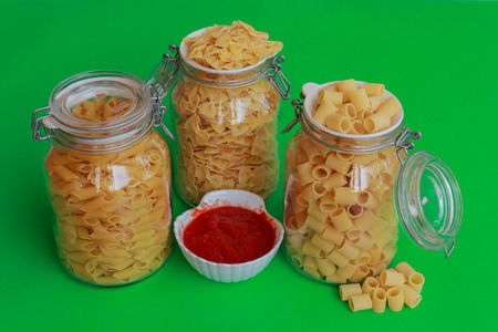 confined: different sizes of pasta to choose from confined in glass jars with bowl of red sauce