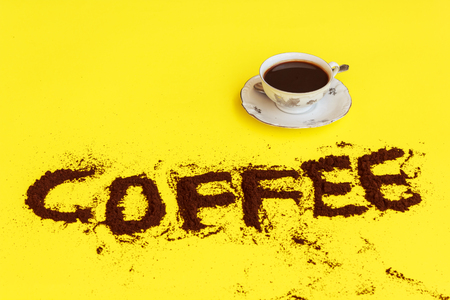 coffee grounds: a cup full of coffee ready to drink with the word coffee drawn with coffee grounds