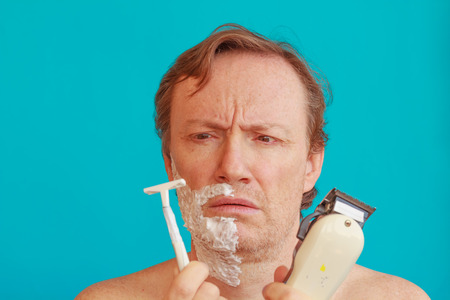 tourquoise: a man with shaving foam about to shave but is undecided Whether to choose or razor razorblade