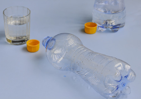 emptied: two bottles of water drained ,with orange cap and the glass