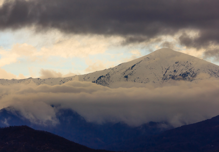 a landscape of striated clouds on a mountain