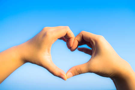 love shape: love shape hand in sky Stock Photo
