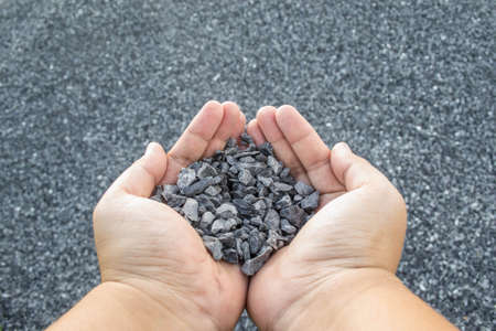 stone background: crushed stone in hand Stock Photo