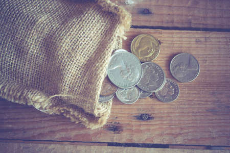 bag with coins on wooden background Stock Photo