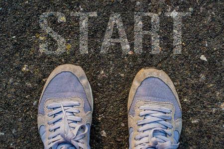 foot marks: text  START written on an asphalt road