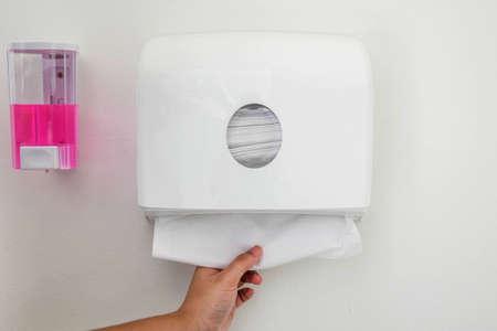 de hand plukken van de weefsels in een dispenser