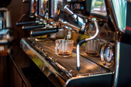 barista preparing fresh espresso on coffee brewing machinery