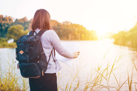The Young woman with backpack standing by the lake, Travel, Freedom, Lifestyle concept Imagens - 133374266