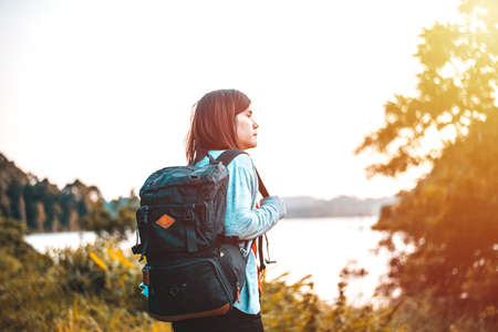 The Young woman with backpack standing by the lake, Travel, Freedom, Lifestyle concept Imagens - 133374267