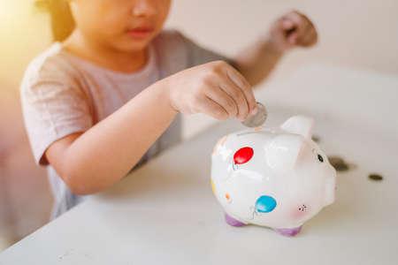 A girl saving coin into piggy bank