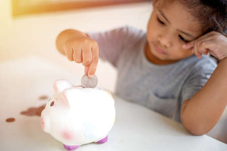 Kid putting coins into piggy bank Stock Photo