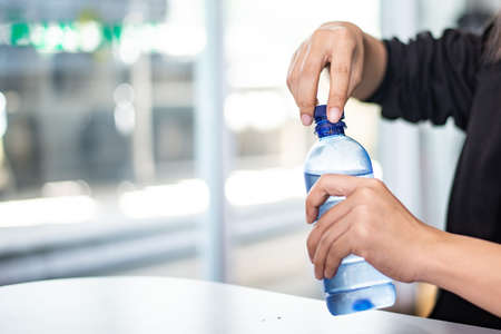 Woman opening bottle of water ,Don't forget to hydrate yourself