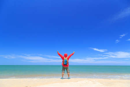 Man rised hands happiness on beach. concept for fredom, worship, travel. Stock Photo