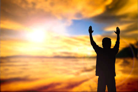 alabanza: Silueta del hombre con las manos levantadas sobre el concepto cruz desenfoque de la religión, el culto, la oración y la alabanza. Foto de archivo