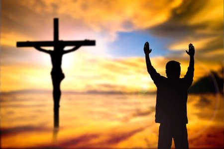 espiritu santo: Silueta del hombre con las manos levantadas sobre el concepto cruz desenfoque de la religión, el culto, la oración y la alabanza. Foto de archivo