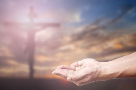 forgiven: Praying Hand and the cross blurred background.