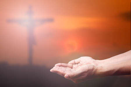 Praying Hand and the cross blurred background.