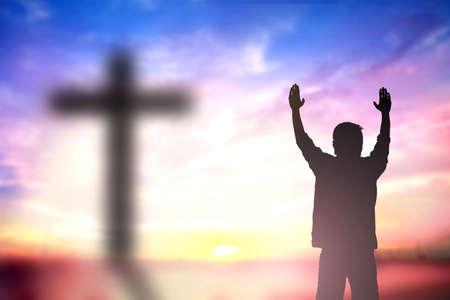 上げられた手を持つ男のシルエット以上宗教、信仰、祈りと賛美のための概念間のぼかし。 写真素材
