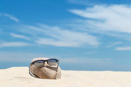 looked: Sunglasses over coconut fruit on sandy beach under hot shiny sun light looked like a happy (tourist) man lying on the beach during holiday summer vacation on wonderful trip under bright blue sky. Stock Photo
