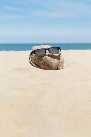 Sunglasses over coconut fruit on sandy beach under hot shiny sun light looked like a happy (tourist) man lying on the beach during holiday summer vacation on wonderful trip under bright blue sky. Stock Photo