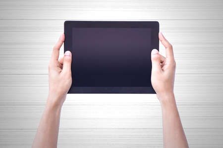 computer devices: Human Hand Hold Tablet over vintage wood background. Stock Photo