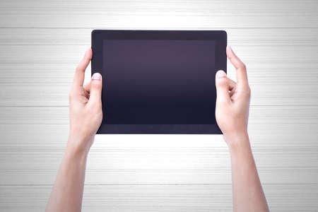 Tablet Hold Mano humana sobre fondo de madera de la vendimia.