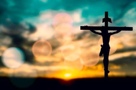 Silueta de Jesús con la Cruz sobre el concepto de la puesta del sol para la religión, el culto, la oración y la alabanza.