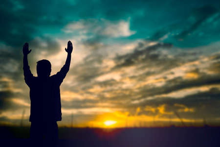 hands reaching: Silhouette of man with raised hands over blur cross concept for religion, worship, prayer and praise.