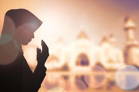 рамадан: Мусульманская женщина молиться и красивый фон. Фото со стока